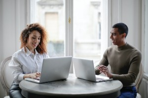 cheerful-young-couple-using-laptops-while-sitting-at-table-3967031
