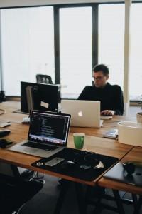 man-sits-behind-computers